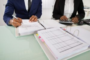 Two individuals working with notebooks showing financial tables