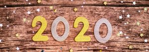 The year 2020 on a rustic wood background surrounded by small colored stars